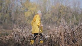 Lichaam van het menselijke lopen zorgvuldig in moeras in gele laarzen en laag stock footage