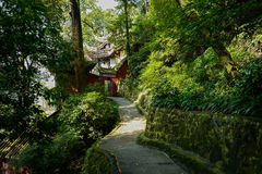Lichen-covered path to ancient Chinese building on mountainside Stock Image