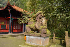 Lichen-covered stone lion before Chinese traditional building in Royalty Free Stock Image