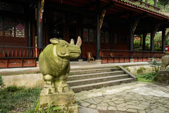 Lichen-covered stone rhino at entrance of ancient Chinese buildi Royalty Free Stock Images