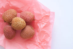Lichi. In a pink paper on bright backgruond Stock Photo