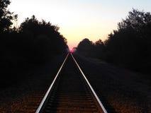 Licht auf Bahnstrecke an der Dämmerung Stockbild