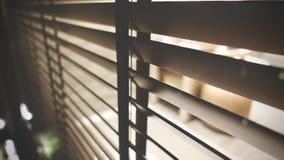 licht binnen badkamers en houten vensterzonneblinden, zonneschijn en schaduw op blind venster en de muur van de Graniettegel stock afbeeldingen