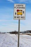 Licht-blinkendes Schulbus-Zeichen entlang einer ländlichen Landstraße Stockbild