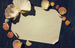 Licht bwooden Schreibtisch mit Seeoberteilen und Blatt Papier Stockbild