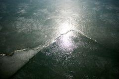 Licht, das auf der Oberfläche des gefrorenen Wassers glänzt lizenzfreie stockfotografie