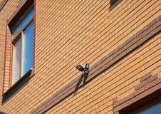 Licht der Bewegungs-Flut-LED auf der Haus-Backsteinmauer im Freien Wie man Bewegungs-Detektor-Beleuchtung wählt und installiert B stockfoto