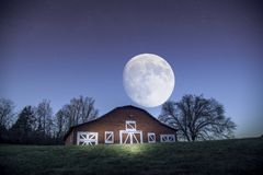 Licht geschilderde schuur tijdens nacht met volle maan en een paar sterren op achtergrond royalty-vrije stock afbeelding