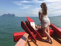 Licht-gevild meisje in strandkleren aan boord van het schip op een hete de zomerdag tegen het overzees van Eilanden Thailand Phu stock afbeelding