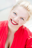 Mooie blonde glimlachende jonge vrouw in rood stock fotografie