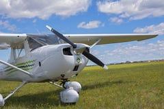Licht privé die vliegtuig op het grasrijke vliegveld wordt geparkeerd Royalty-vrije Stock Afbeeldingen