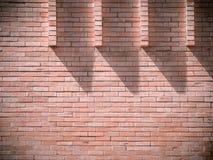 Licht und Schatten auf der Backsteinmauer bei 10 O-` Uhr Stockbilder
