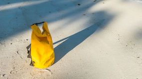 Licht und Schatten auf sandigem Strand mit gelber wasserdichter Tasche Lizenzfreie Stockfotos