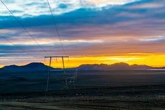 Licht van zonsondergang bij de berg met de hoogspanningskabel stock afbeeldingen