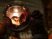 Licht von Kerzen, von Kiefernkegeln und von Büchern stockfoto