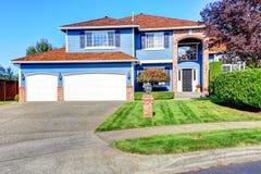 Lichtblauw huis buiten met baksteenversiering en tegeldak Stock Foto