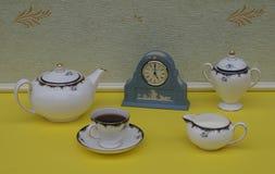 Lichtblauw Wedgwood-horloge Jasperware met toegepaste hulpplaat van witte klei, naast een teaset royalty-vrije stock foto