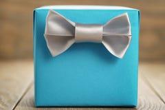 Lichtblauwe giftdoos met minimalistic zilveren lintboog op houten Stock Afbeeldingen