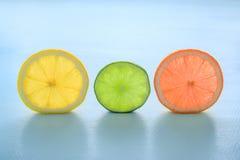 Lichtdurchlässige Scheiben der orange Pampelmuse u. des Kalkes der Zitrone auf blauem BAC Stockfotografie