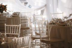 Lichtdurchlässige Stühle in einem Heiratszelt stockbild