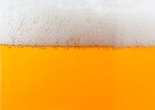 Lichte bierachtergrond met schuim stock foto's