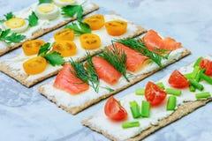 Lichte de zomersnack Kleine sandwiches met verschillende vullingen Tomaten, kruiden en rode vissen Heerlijk brood met zacht royalty-vrije stock foto's