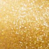 Lichte het onduidelijke beeldachtergrond van de Kerstmis gouden gloed bokeh stock afbeelding