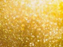 Lichte het onduidelijke beeldachtergrond van de Kerstmis gouden gloed bokeh royalty-vrije stock afbeelding