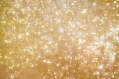 Lichte het onduidelijke beeldachtergrond van de Kerstmis gouden gloed bokeh royalty-vrije stock foto