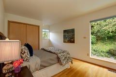Lichte ivoorslaapkamer met groot venster Stock Afbeelding