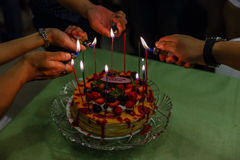 Lichte Kaarsen op de Rouwbandcake die op bovenkant met Gemengde Bessen en Aardbeisaus Royalty-vrije Stock Afbeelding