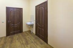 Lichte lege gangzaal met houten vloer, bruine deuren en gootsteen School, bureau of kliniekbinnenland royalty-vrije stock fotografie