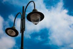 Lichte post met twee bollen en blauwe bewolkte hemelachtergrond Openluchtstraatlantaarns Gietijzerlamp Grote lantaarn Verlichting stock afbeeldingen