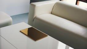 Lichte ruimte met witte bank, stoelen en koffietafel op z'n gemak met dun gouden vakje stock video