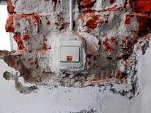 Lichte schakelaar in een muur met verwijderd pleister en zichtbare bakstenen royalty-vrije stock foto's