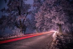 Lichte slepen bij nacht in de winter, bevroren weg Stock Afbeelding
