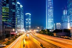 Lichte slepen op de straat met de moderne bouw Stock Foto's