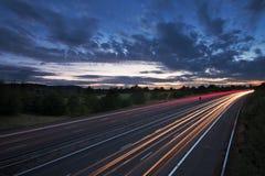 Lichte slepen op een autosnelweg bij schemer Stock Foto