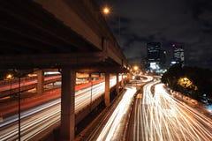 Lichte slepen op stedelijke straat en brug bij nacht Stock Foto