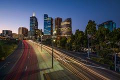 Lichte slepen van verkeer met verlichte wolkenkrabbers van Melbourn stock afbeelding