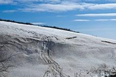 Lichte sneeuwhelling op een achtergrond van blauwe hemel Stock Foto