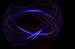 Lichte spiraalvormige, rode en blauwe lijnen op een zwarte achtergrond Stock Afbeelding