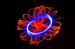 Lichte spiraalvormige, rode en blauwe lijnen op een zwarte achtergrond Royalty-vrije Stock Afbeeldingen