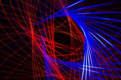 Lichte spiraalvormige, rode en blauwe lijnen op een zwarte achtergrond Stock Foto