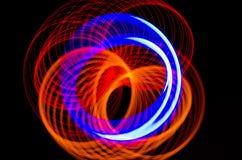 Lichte spiraalvormige, rode en blauwe lijnen op een zwarte achtergrond Stock Afbeeldingen