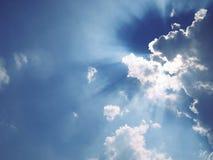 Lichte straal van zon achter wolk in de blauwe hemel Stock Foto's