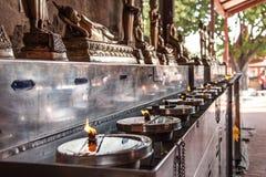 Lichten van Boeddhistische oliekaarsen bij de tempel Stock Fotografie