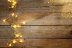 Lichten van de Kerstmis de warme gouden slinger op houten rustieke achtergrond stock fotografie