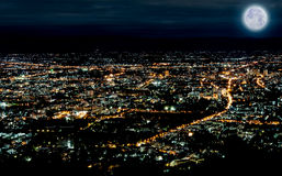 Lichten van stad in nachtscène met blauwe maan Royalty-vrije Stock Foto's