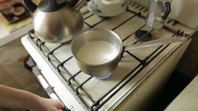 Lichter einer jungen Frau einer Gaskochplatte mit Match auf der Küche Mädchenheizungsmilch in einer Wanne für Hafermehl kochen stock video